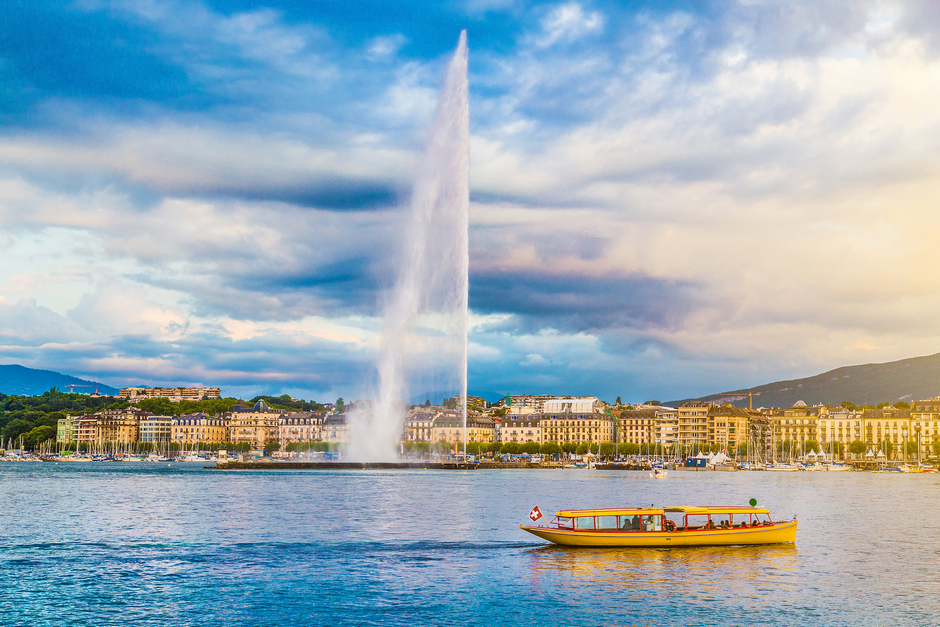 Geneva city with lake and jet d'eau and boat and mountains in background